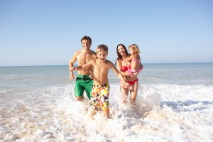 bigstock-Young-family-play-on-beach-13920431-300x200
