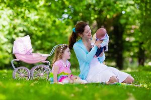 Mother And Kids Enjoying Staycation Picnic Outdoors