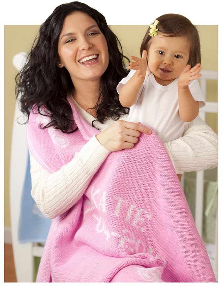 Mom and baby with girl's pink personalized baby blanket gift.