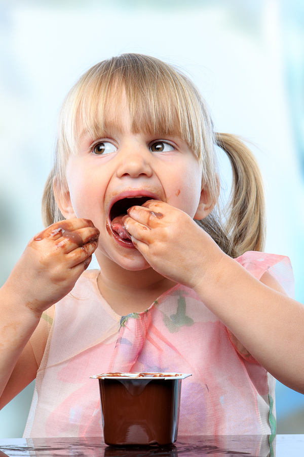 Cute Girl Eating Chocolate Yogurt With Hands.