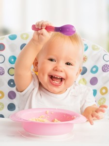 cheerful happy baby child eats itself with a spoon